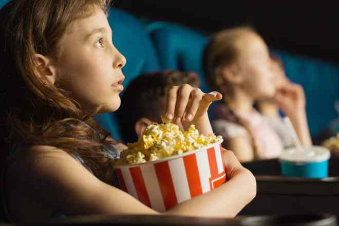 Close up shot of a pretty little girl grabbing popcorn from the bucket while watching a movie at the cinema looking entertained and fascinated.