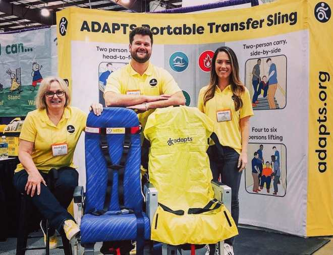 Robin Wearley and a man and woman dressed in yellow ADAPTS t-shirts standing behind airplane seats, one of which has an ADAPTS sling draped over it.