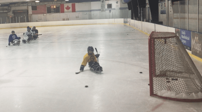 Charlie at the ice rink wearing a yellow jersey and sitting in a hockey sled. He is about to strike a puck toward the goal.
