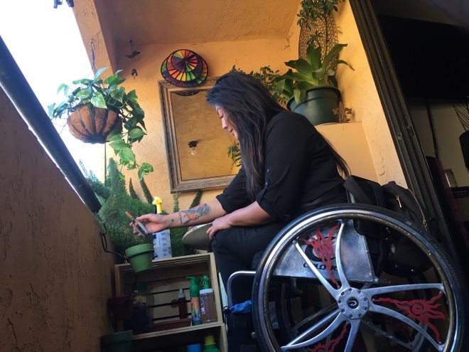 Side view of Hydred Makabali in her Colors wheelchair tending to her plants on her balcony.