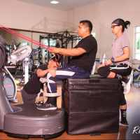 A paralyzed man uses a Power Plate machine with the help of two trainers.