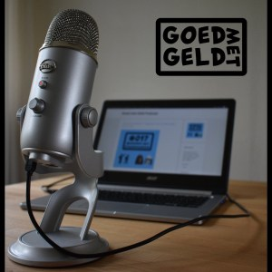 On the picture you see a brown table with a grey microphone and a grey laptop on it. On the laptop the Goed Met Geld website is hows. It's mostly white text and a vague blue image. On the right upper corner it says Goed met Geld with a black line around it. It's their logo.