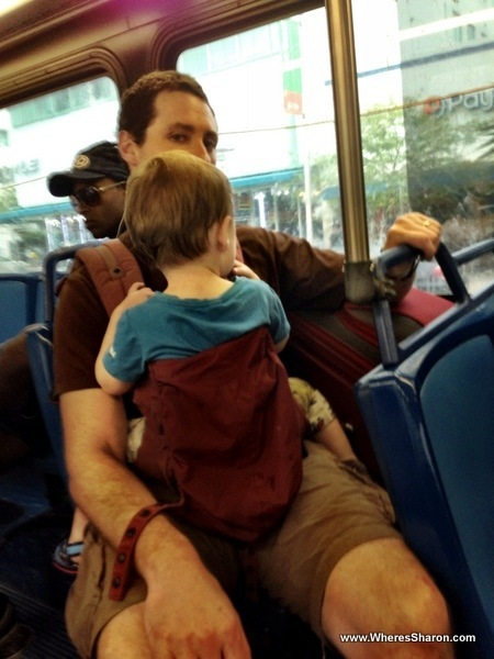 Baby and man with a suitcase on a miami bus