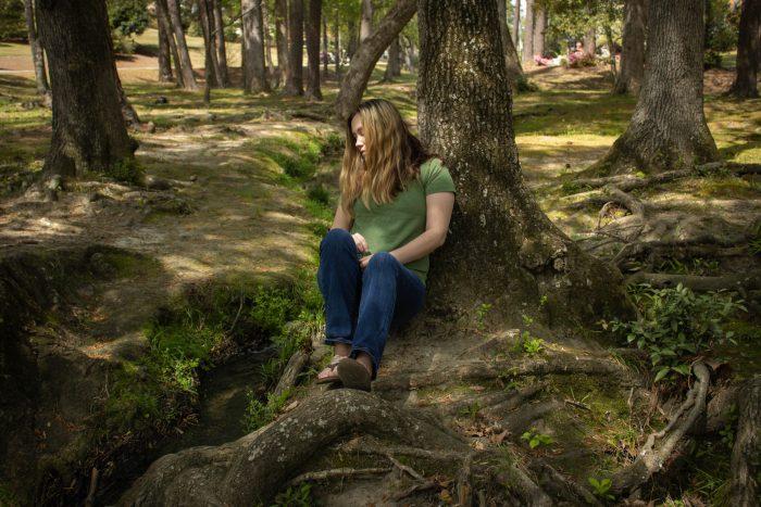 woman sitting beside a creek
