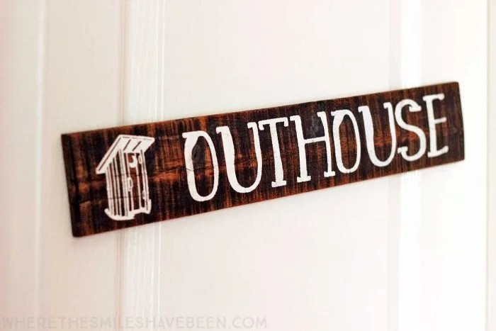 What a cute sign for a bathroom door in a rustic woodland nursery! Take a tour of this navy & orange modern woodland nursery! | Where The Smiles Have Been