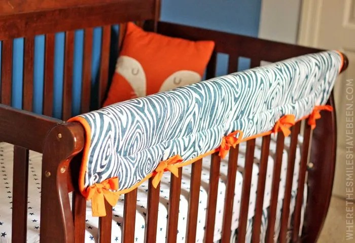 LOVE this woodgrain crib rail guard! It's perfect for a rustic or woodland nursery! Take a tour of this Navy & Orange Modern Woodland Nursery! | Where The Smiles Have Been