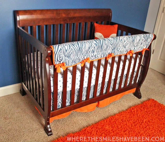 LOVE this woodgrain crib rail guard and crib skirt! It's perfect for a rustic or woodland nursery! Take a tour of this Navy & Orange Modern Woodland Nursery! | Where The Smiles Have Been