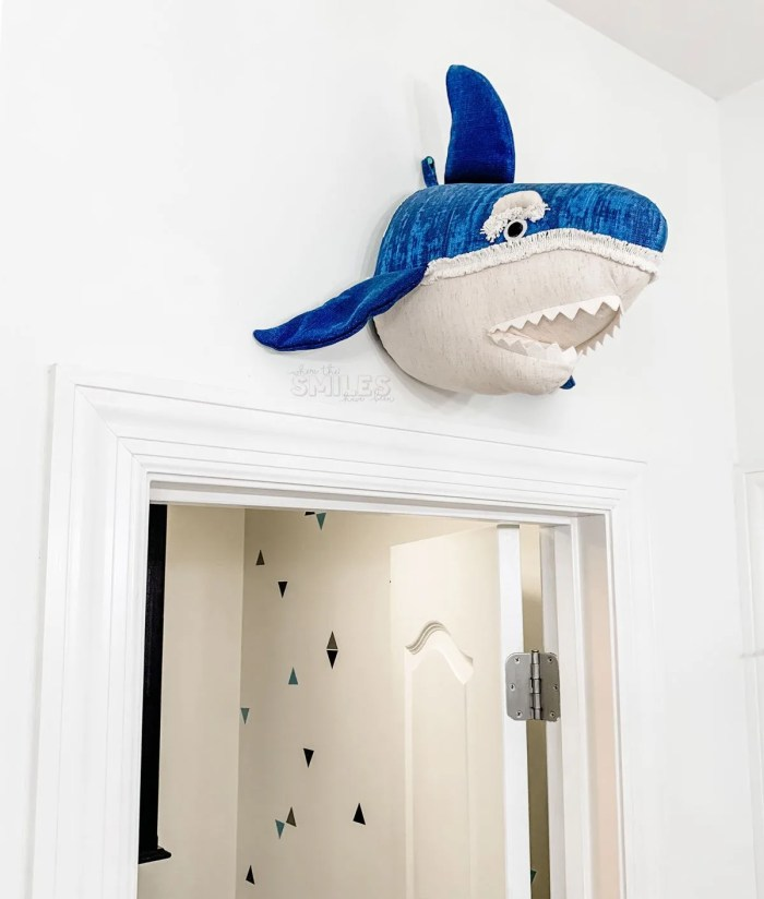 This kids bathroom makeover is SO COOL and was SO EASY! Kids Bathroom Makeover: Shark Attack! | Where The Smiles Have Been #bathroom #bathroommakeover #kidsbathroom #kidsroom #shark #sharkbathroom #paintedcabinets #bluebathroom #bluecabinets #vinyl #indoorvinyl #vinylwallpaper #wallpaper #makeover #easymakeover #DIYmakeover #beforeandafter #beforeandafterbathroom #sharkhead