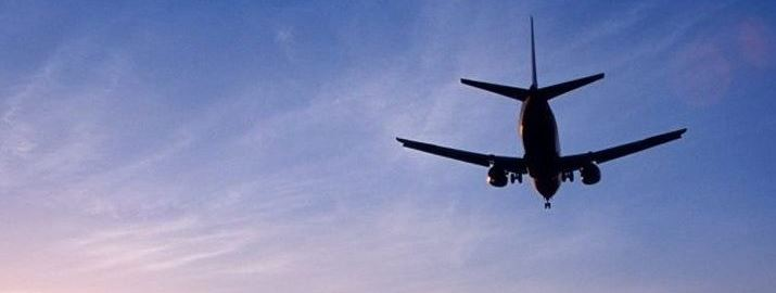 Aircraft flies against blue sky