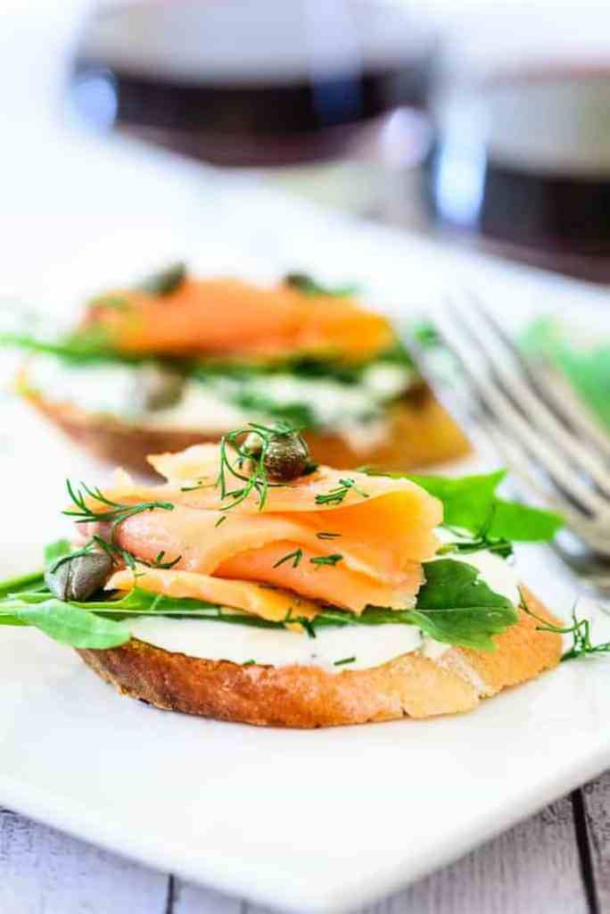 Smoked Salmon Cream Cheese Bruschetta is a wonderful finger food prepared by topping baguette with smoked salmon, herbs, cream cheese, rocket leaves.