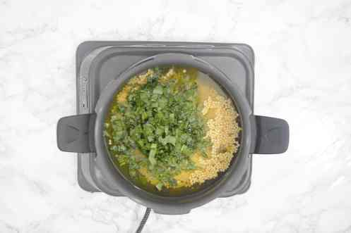 Dal added in a pressure cooker along with salt, turmeric powder, water and chopped spinach.