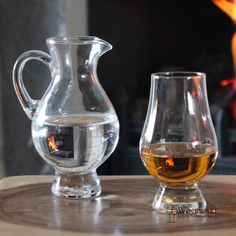 A small water carafe adjacent to a half full glass of whisky suggesting that water & whisky have been mixed.