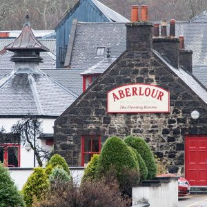 An image of the exterior of Fleming Rooms at Aberlour Distillery where aberlour a'bunadh is made. The iamge is of the gable end of a dark stone build with red window trim and red doors. The word Aberlour is in a sign attached to the building.