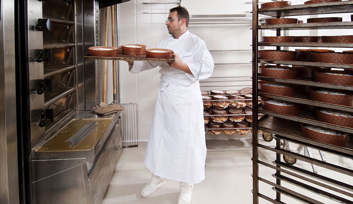 Pastry Chef, takes away the panettone from the oven freshly cooked