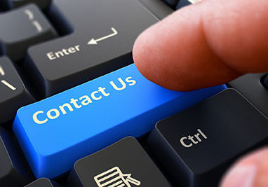 Contact Us - Written on Blue Keyboard Key. Male Hand Presses Button on Black PC Keyboard. Closeup View. Blurred Background.