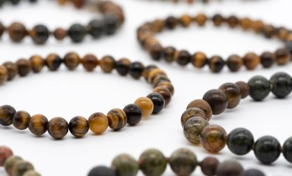 Bracelet made of tiger eye semiprecious stone on a white background, close-up, selective focus.