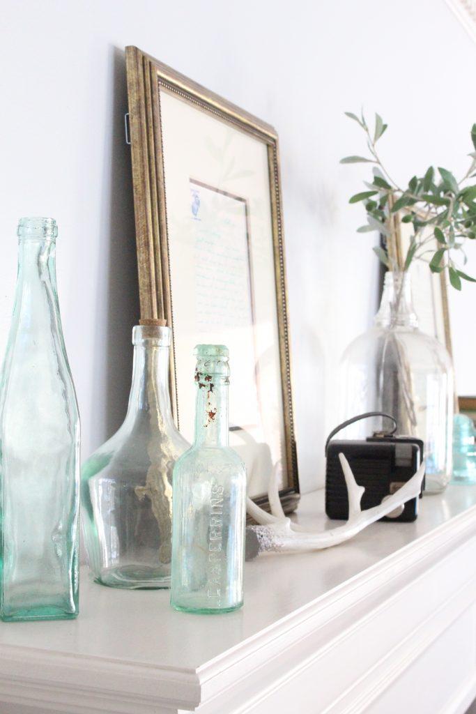 spring mantel-bottles- insulators- vintage cameras- mantel decor- decorating a mantel for spring- mantles- keepsakes- how to use keepsakes in decor- using bottles in decor