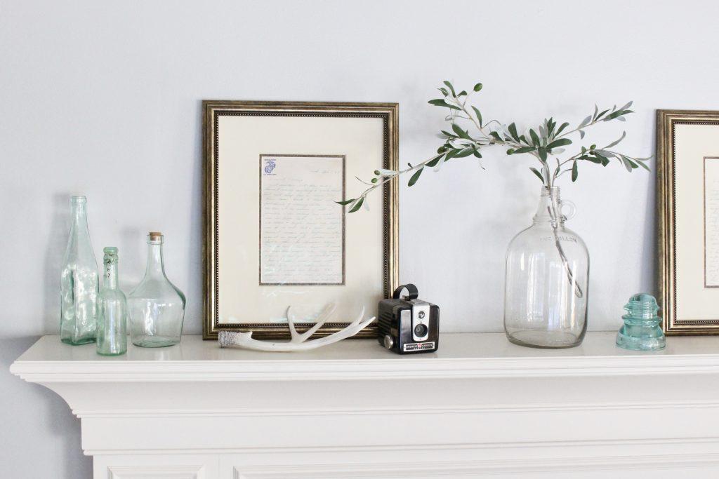 spring mantel-bottles- insulators- vintage cameras- mantel decor- decorating a mantel for spring- mantles- keepsakes- how to use keepsakes in decor- framed letters- vintage decor on display