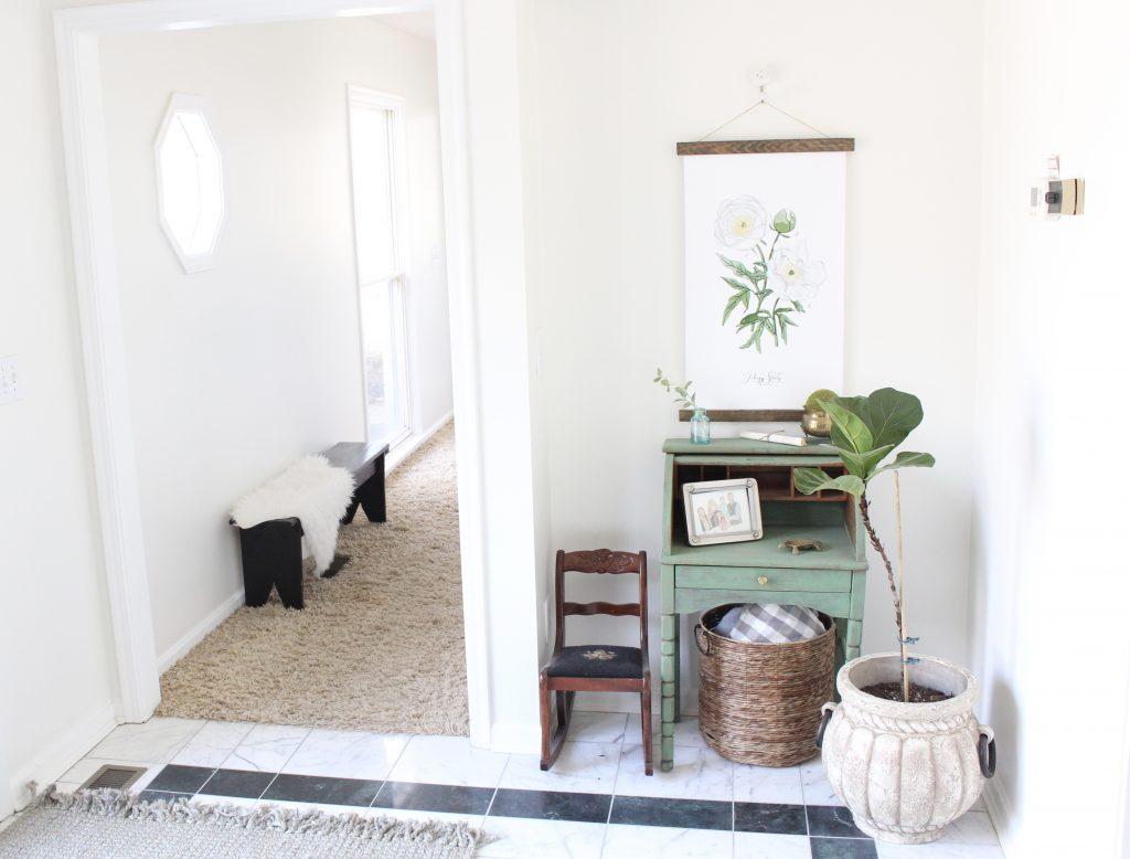 green desk- vignette- spring decor- filling a nook- fiddle fig leaf tree- brass animals- green painted furniture- vintage bottles- hanging wall canvas