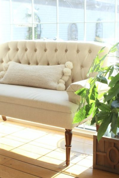 A new tufted settee in the dining room adds a cozy spot for morning coffee. #settee #diningroom dining room- decor- furniture- neutral settee- pom pom pillow- settee in the dining room
