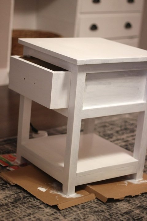 Painting a side table with two coats of white paint