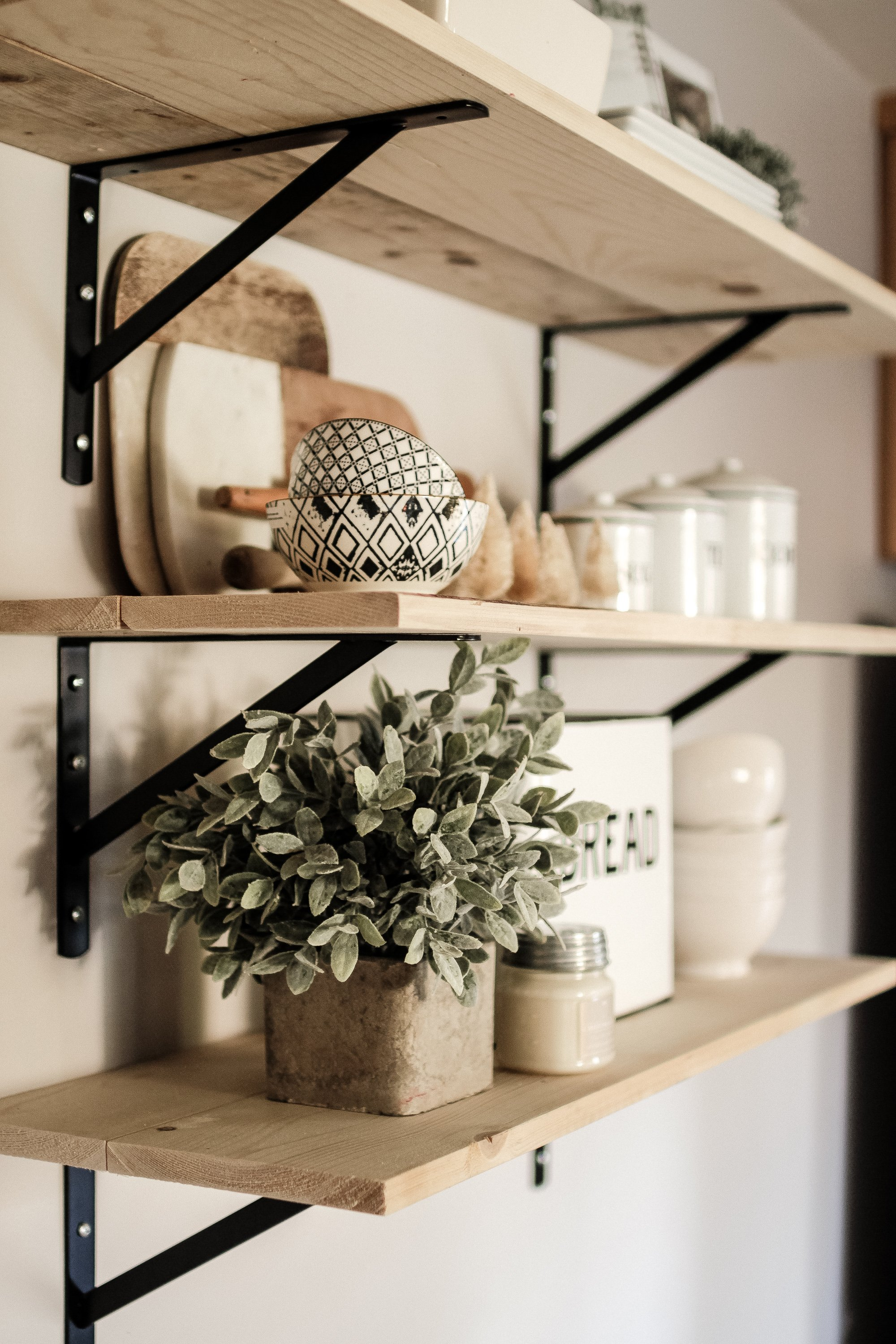 How To Decorate A Shelf. Our Modern Farmhouse Shelving in our Kitchen and how I styled it with greenery, cutting boards, dishes and canisters.