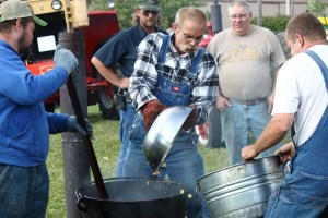 Men at the 2016 Whitley County 4-H fair making kettle corn in a large cast iron kettle over a fire while other fair visitors watch