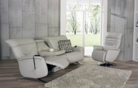 himolla Cygnet Sofa, shown in pale grey leather, in reclined position, with trapezoidal table on the curved 3 seater, shown in living room setting.