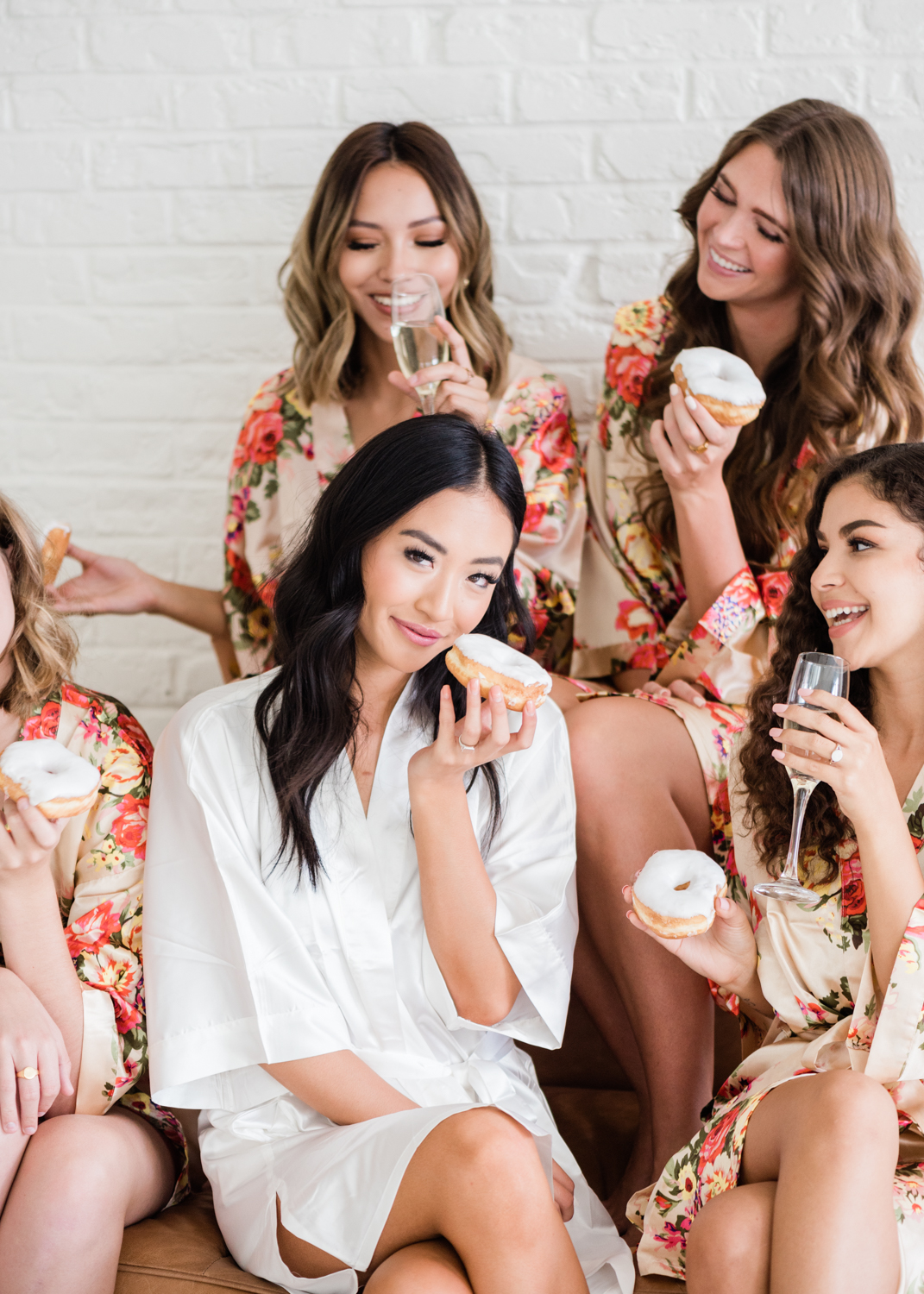 group of bridesmaids with bride drinking champagne