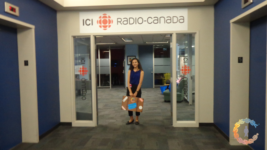 Marisa with suitcase under CBC sign