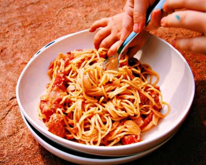 Vegan Tomato Cream Sauce and Spaghetti in a white bowl and terracotta background with two children's hands in the bowl trying to get the spaghetti