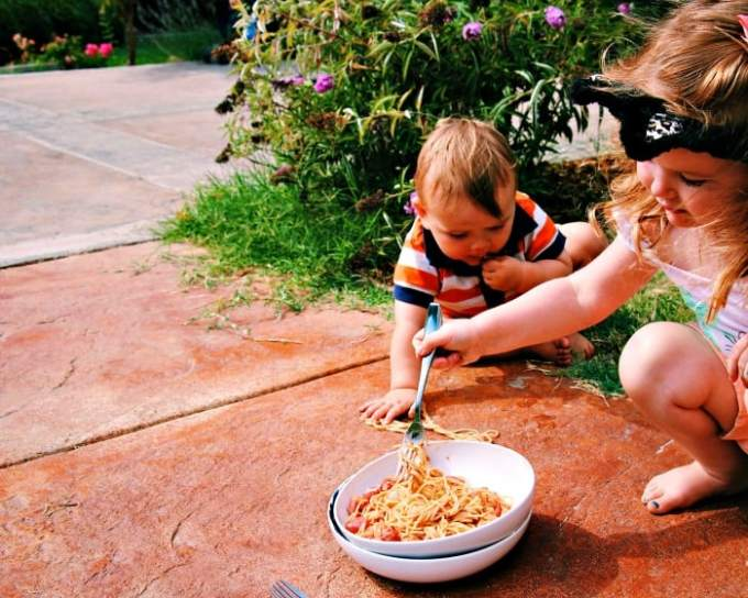 Vegan Tomato Cream Sauce and Spaghetti in a white bowl and terracotta background with two children eating from the bowl