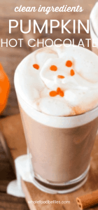 Thick and Creamy Pumpkin Hot Chocolate in a tall glass on a wooden board with orange sprinkles on top
