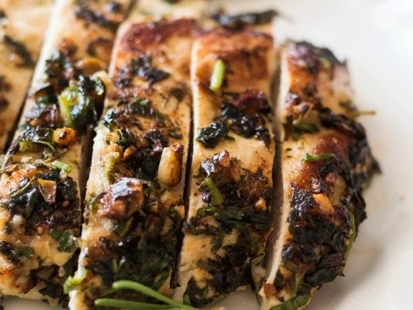 Sliced Sage and Macadamia Nut Chicken Breasts on a wooden board surrounded by sprigs of fresh rosemary