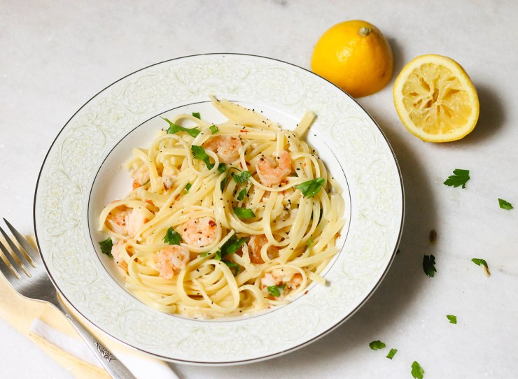 Garlic prawn scampi recipe with linguine on a marble counter with squeezed lemon