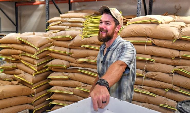 Nathan Brett, co-owner of DaySpring Farms near Danielsville, stands in the grinding room in front of stacks of 50-pound bags of finished products ready for sale.  DaySpring Farms is an organic certified farm that grows, harvests and grinds grain on site.  (Chris Hunt for The Atlanta Journal-Constitution)
