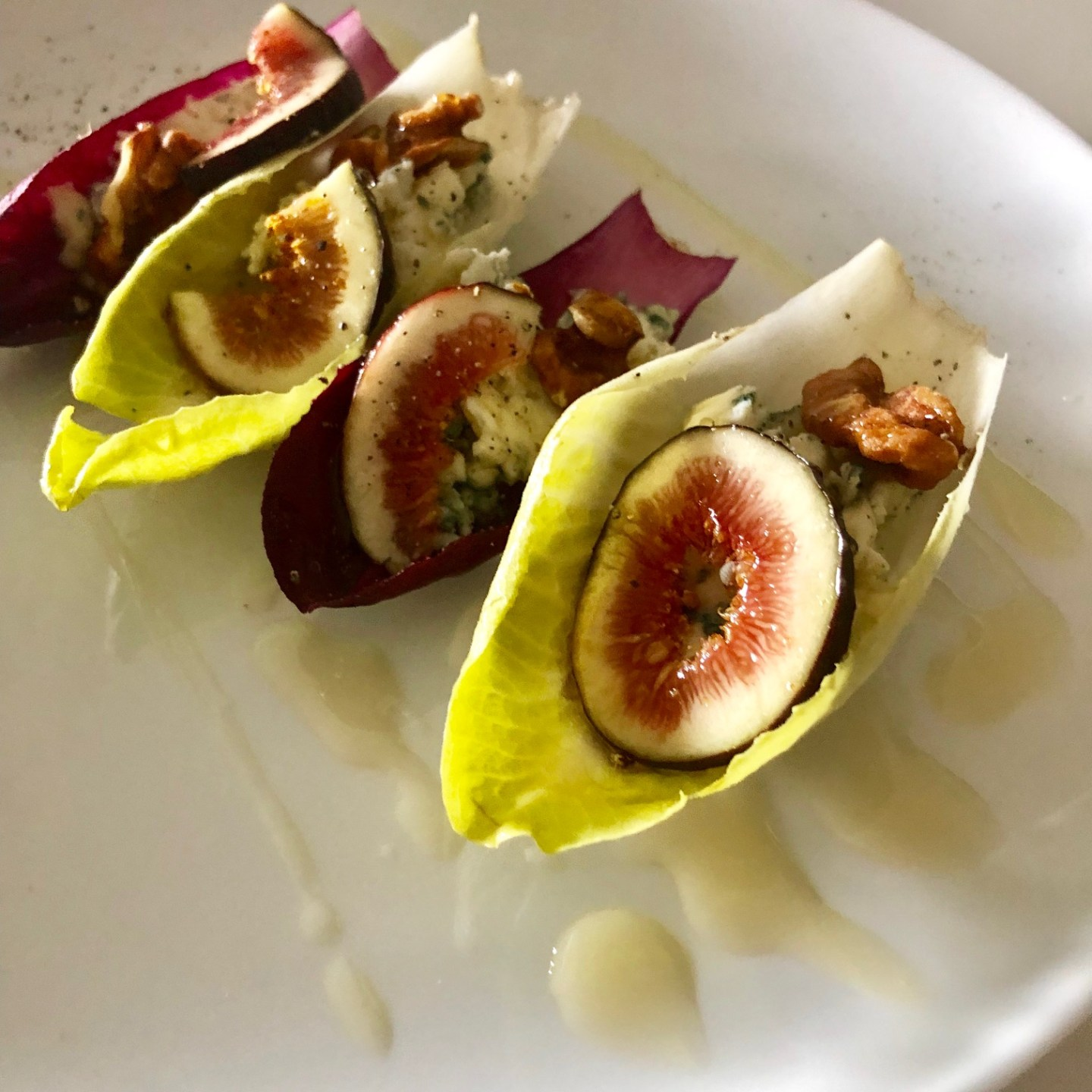 Fig, blue cheese, candied walnut, and honey in endives