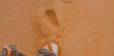 A woman walking in the desert by Toa Heftiba via unsplash