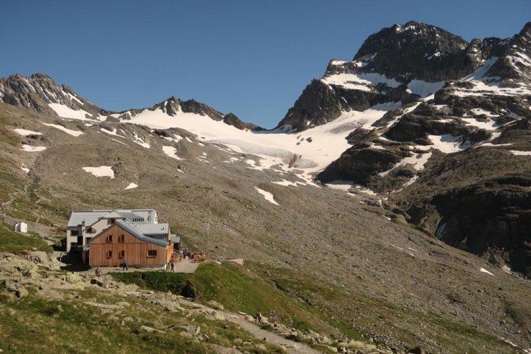 Das Bild zeigt den Ausblick beim Klettern Wiesbadener Hütte. Man sieht eine große Schutzhütte, im Hintergrund hochalpines Gelände, einen weißen Gletscher und hohe Berge vor blauem Himmel.
