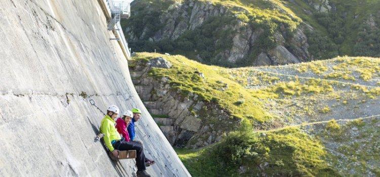 Das Bild zeigt eine Szene zum Thema Klettern Montafon. Drei Klettersteig Geher sitzen auf einer Bank mitten auf einer Staumauer.