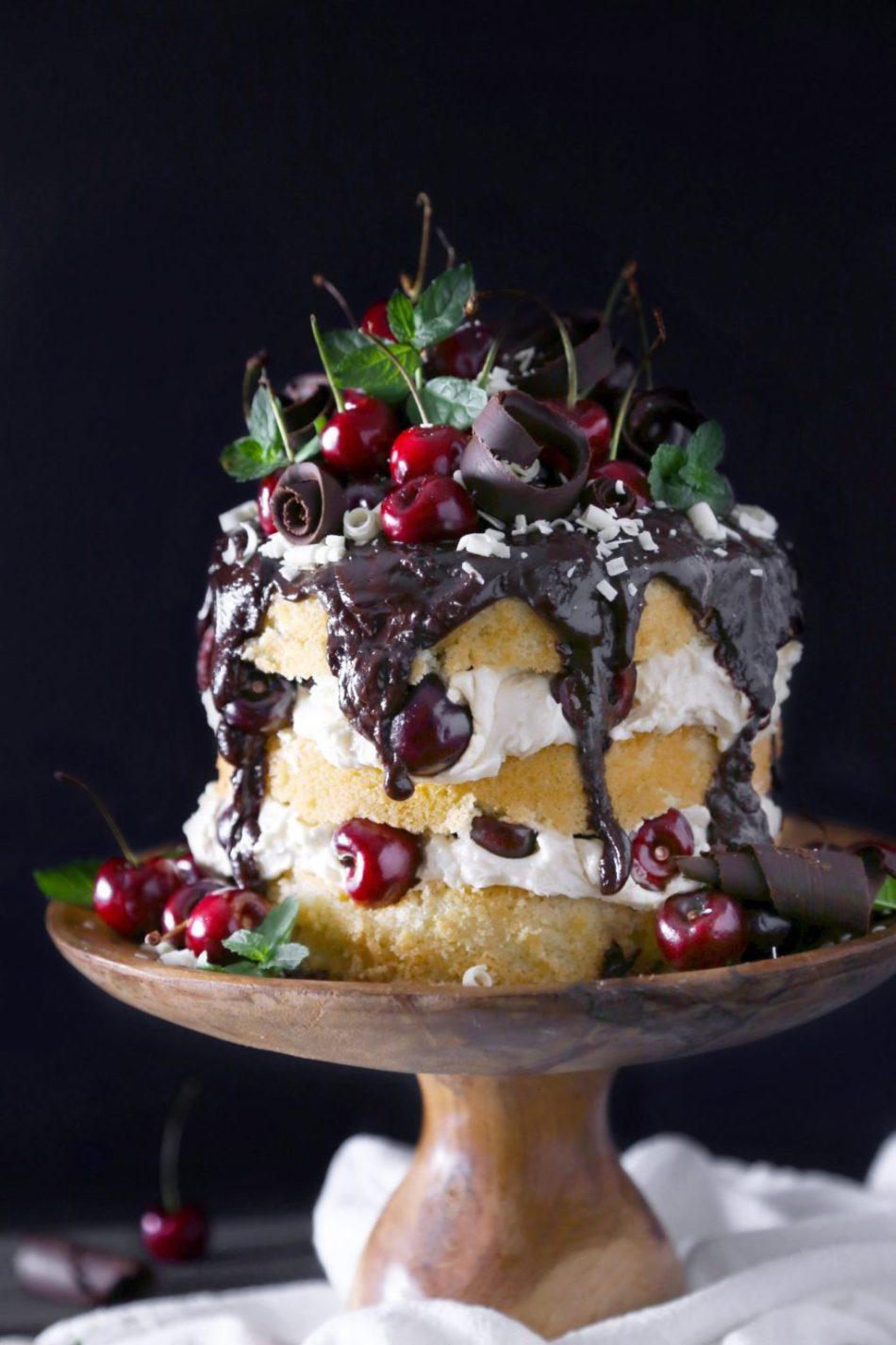 White Forest Cake | Gluten, dairy, and refined sugar free vanilla cake topped with white chocolate buttercream, cherries, and dark chocolate ganache.