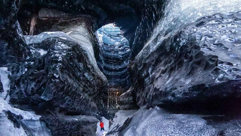 blue and black natural ice cave under Katla Volcano
