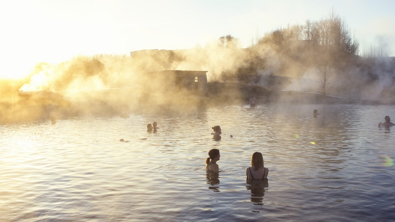 people relaxing in the secret lagoon geothermal hot spring in Iceland