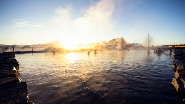 People swimming in the Secret Lagoon geothermal hot spring in Iceland
