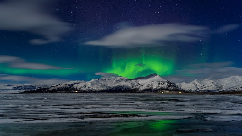 northern lights dancing over the mountains in Iceland