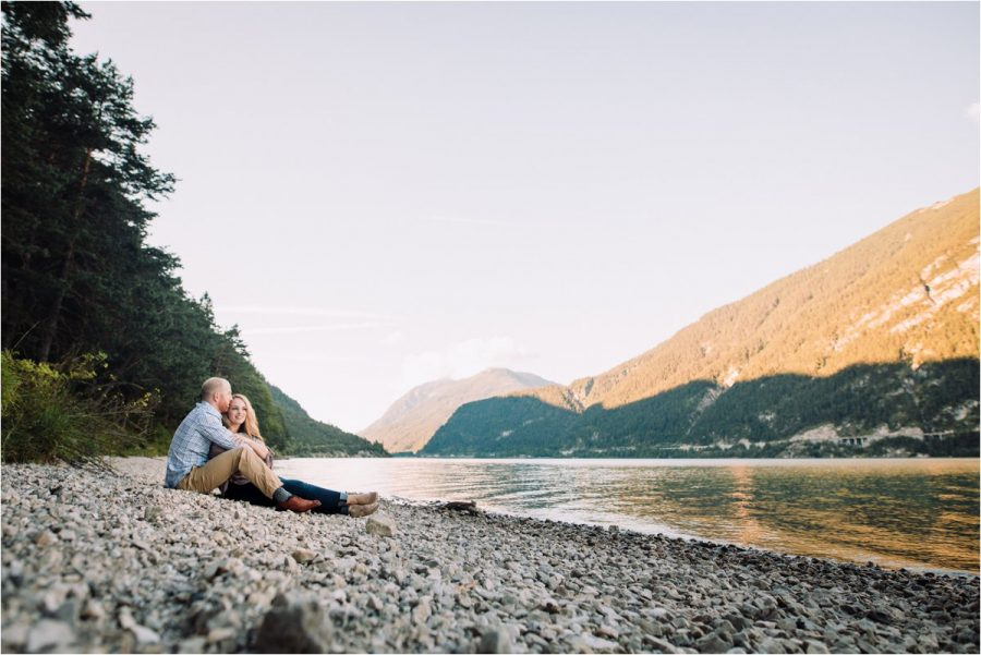 Couple sitting on the shore of a mountain lake in Austria