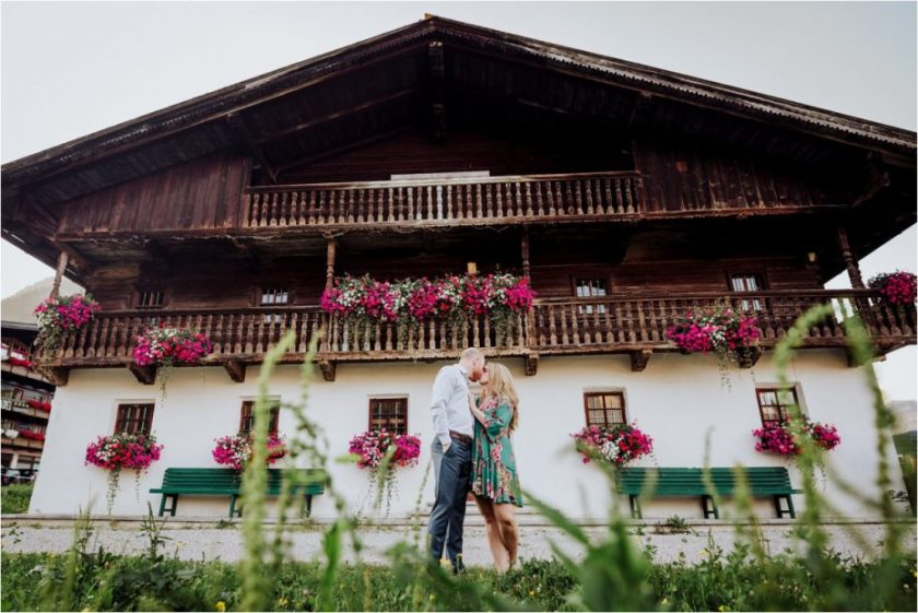 Couple kissing in front of old Austrian wooden farm house