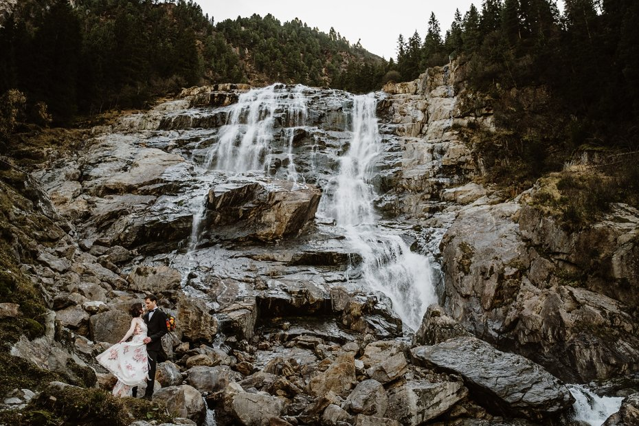 Elopement locations in Europe, a couple stands underneath a waterfall in Tirol, Austria