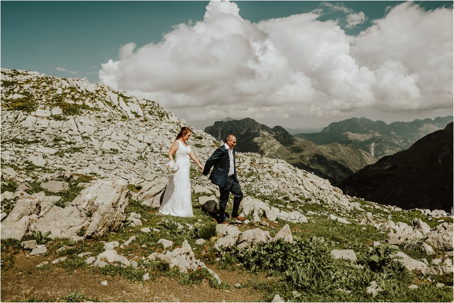 An adventure session in Lech, the bride and groom walk down a hiking trail Image by Wild Connections Photography
