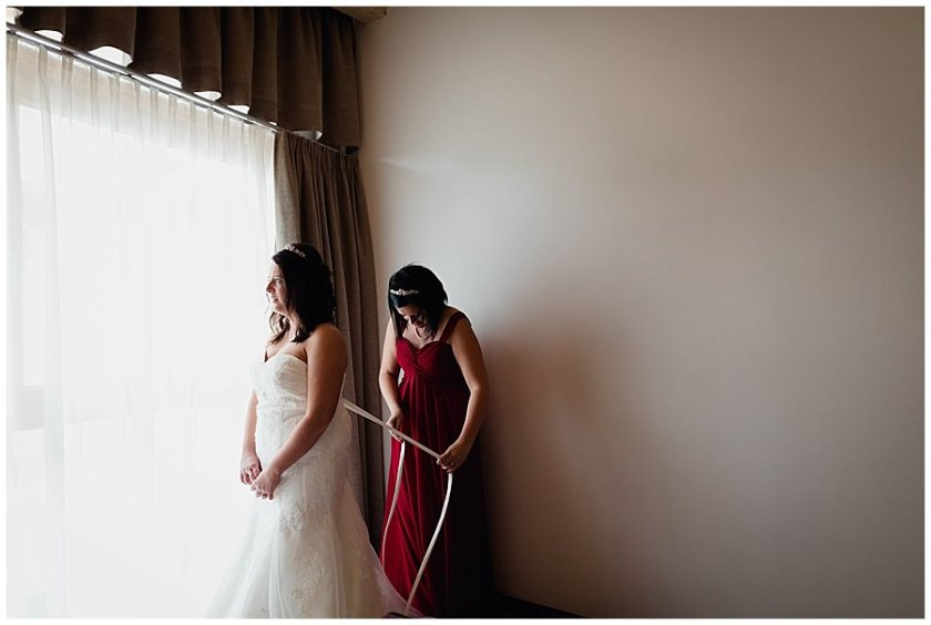 Bride Michelle stands by the window as her wedding dress is laced up